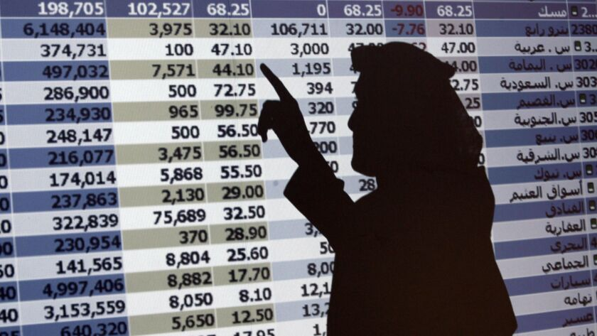FILE - In this Oct. 7, 2008 file photo, the shadow of a Saudi trader is seen on a stock market monit