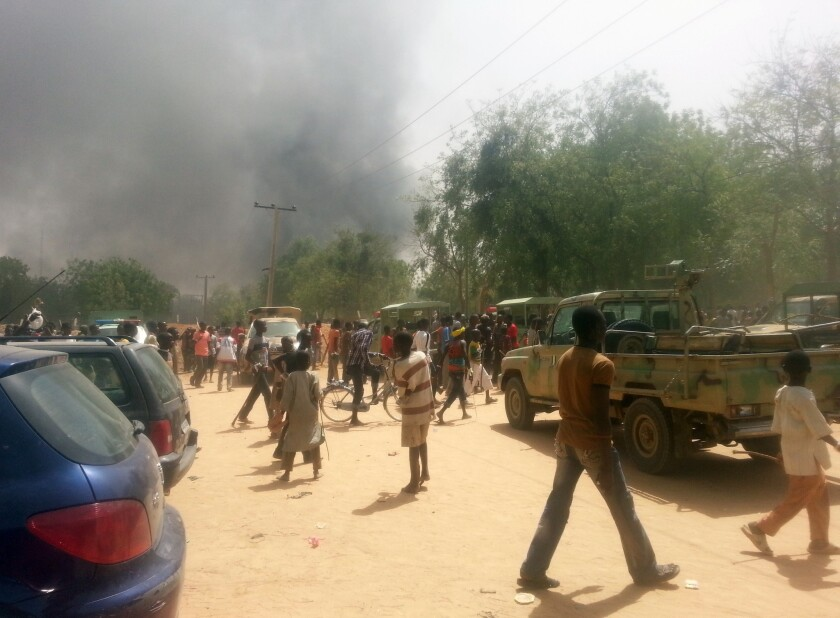 People look at smoke rising after suspected Boko Haram Islamists attacked a military base in the northeast Nigerian city of Maiduguri.