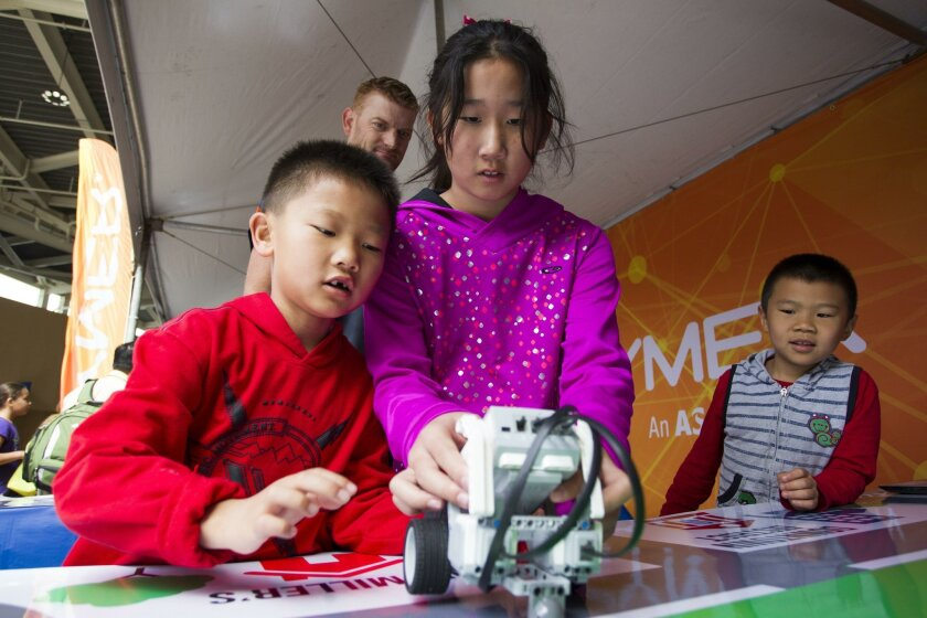 At the Cymer booth, (L to R) Elvin Zhang, Jocelyn Zhang, Ryan Liu play with the Lego Mindstorm Robotics demo.