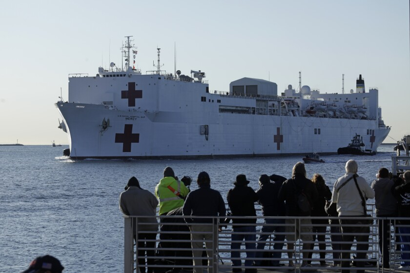 A crowd gathers to watch the arrival of the USNS Mercy hospital ship in San Pedro, Los Angeles