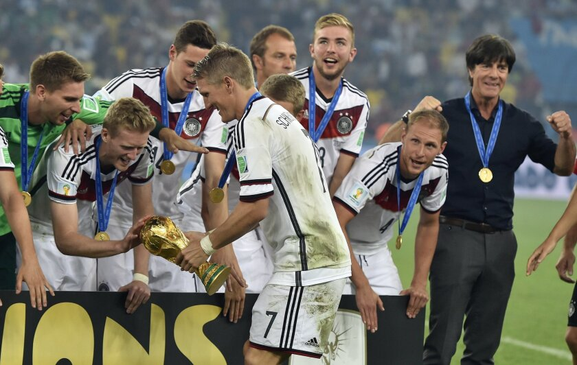 Germany's Andre Schuerrle touches the trophy held by Bastian Schweinsteiger as they celebrate after the World Cup final soccer match between Germany and Argentina at the Maracana Stadium in Rio de Janeiro, Brazil, Sunday, July 13, 2014. Germany won the match 1-0. (AP Photo/Martin Meissner)