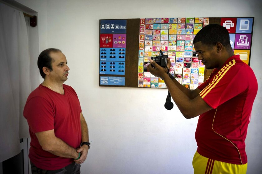 Lian Marrero takes a portrait of his client, Miami-based Cuban Javier Fontanella, for his Cuban citizenship application in Havana, Cuba, Thursday, May 26, 2016. Marrero, a 27-year-old electrician who runs a busy photo studio in the front room of the home he shares with his wife, said he offered cli
