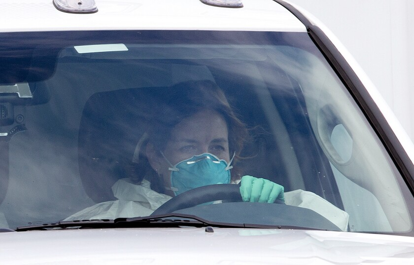 A woman in protective clothing drives an ambulance after departing Dobbins Air Reserve Base in Marietta., Ga. en route Emory University Hospital in Atlanta.