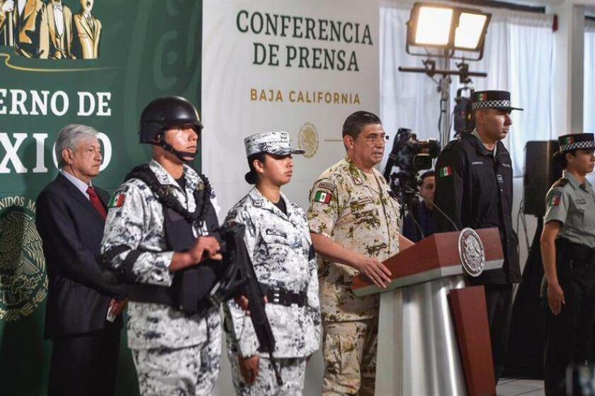 El secretario de la Defensa Nacional (c), general Luis Cresencio Sandoval González (c), habla junto al presidente de México, Andrés Manuel López Obrador (i-atrás), durante una rueda de prensa matutina este miércoles, en la ciudad de Tijuana, en el estado de Baja California (México). EFE