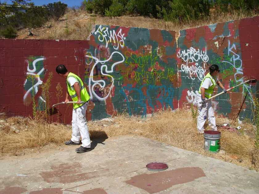 "Urban Corps of San Diego County workers who are part of the program's ""Graffiti Erasers"" clean up defaced walls in San Diego. Urban Corps will be deploying two people in El Cajon after their contract was approved by the City Council."