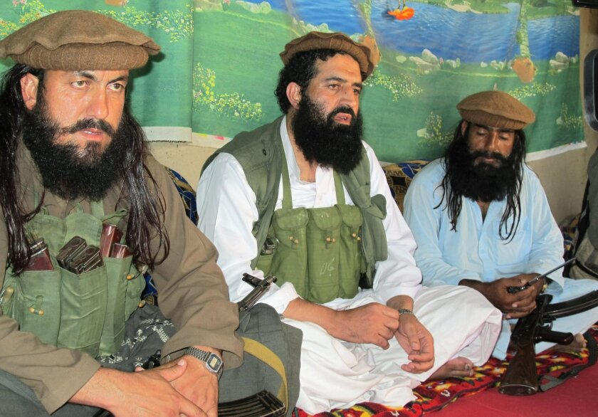 FILE - In this Saturday, Oct. 5, 2013 file photo, Pakistani Taliban spokesman Shahidullah Shahid, center, flanked by his bodyguards, talks to reporters at an undisclosed location in Pakistani tribal area of Waziristan along Afghanistan border. The Pakistani Taliban announced Saturday that the group