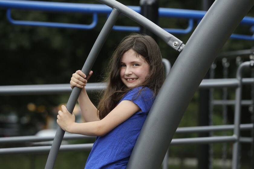 Sophia Garabedian, 6, of Sudbury, Mass., who contracted Eastern Equine Encephalitis in 2019, stands for a photograph on a playground, Wednesday, July 8, 2020, in Sudbury. As the coronavirus pandemic subsides for now in the hard hit Northeast, public health officials in the region are bracing for another mysterious virus: Eastern Equine Encephalitis, or EEE, a rare but severe mosquito-borne virus. (AP Photo/Steven Senne)