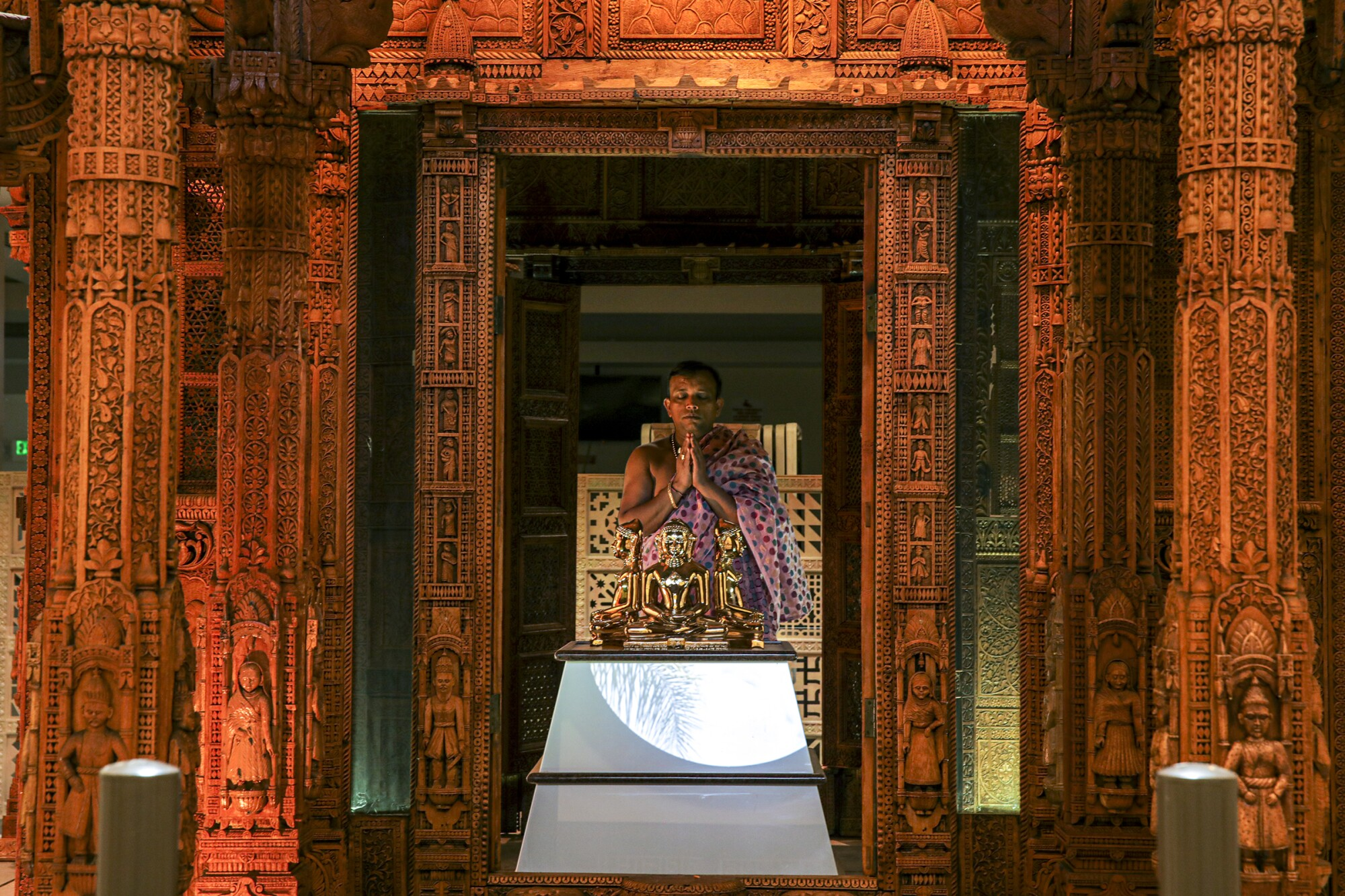 A man clasps his hands together in prayer inside a temple with ornate wooden columns