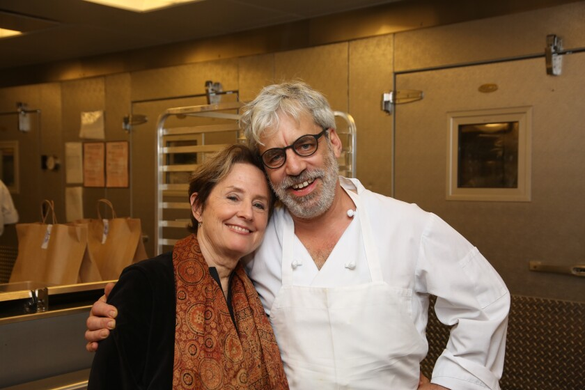 A man wearing a white apron has his arm around a woman in a scarf in a restaurant kitchen.