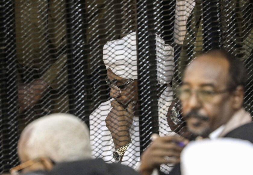 FILE - In this Aug. 24, 2019 file photo, Sudan's autocratic former President Omar al-Bashir sits in a cage during his trial on corruption and money laundering charges, in Khartoum, Sudan. A top Sudanese official said Monday, Feb. 11, 2020, that transitional authorities and rebel groups have agreed to hand over al-Bashir to the International Criminal Court for war crimes, including mass killings in Darfur. Since his ouster in April, al-Bashir has been in jail in Sudan's capital, Khartoum over charges corruption and killing protesters. (AP Photo, File)
