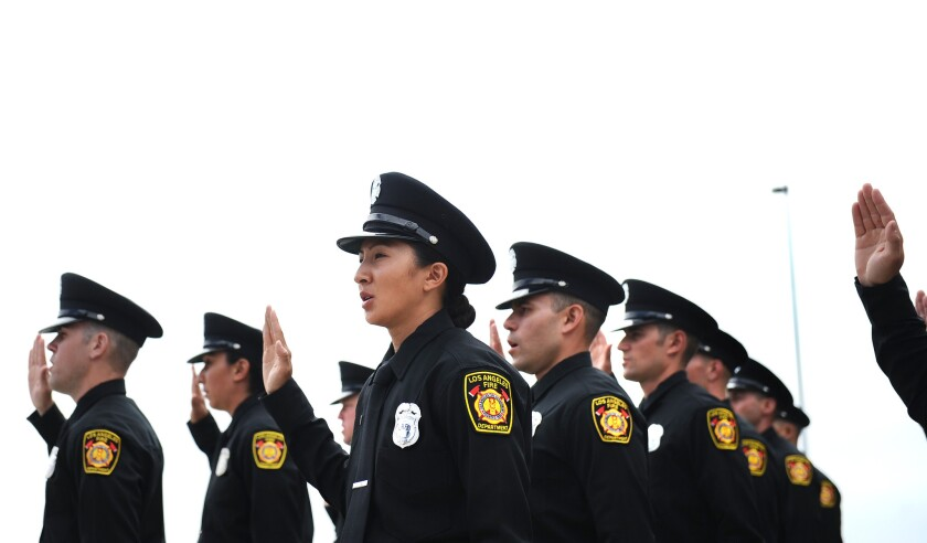 LAFD drill tower graduate Ahn Nguyen, center, takes the oath during graduation ceremonies in August.