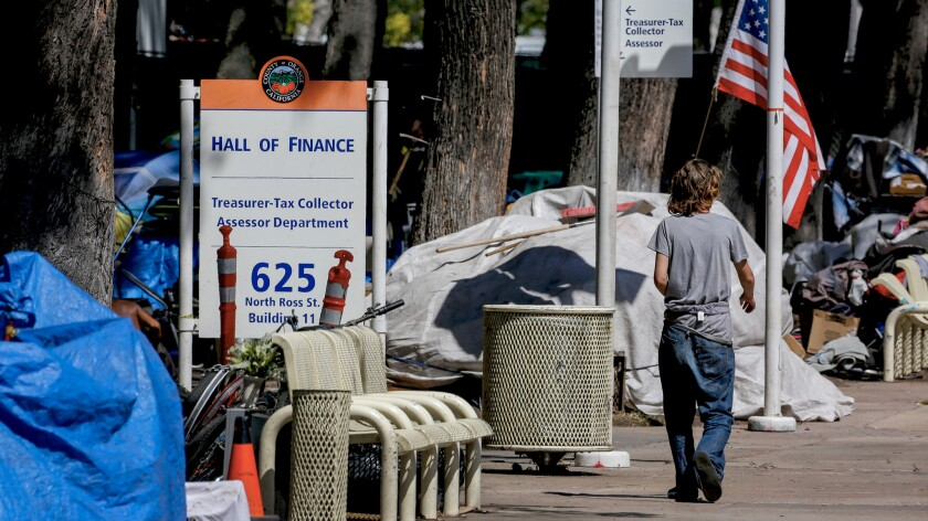 A homeless person walks past one of the encampments next to the Hall Of Finance in the Civic Center Plaza.