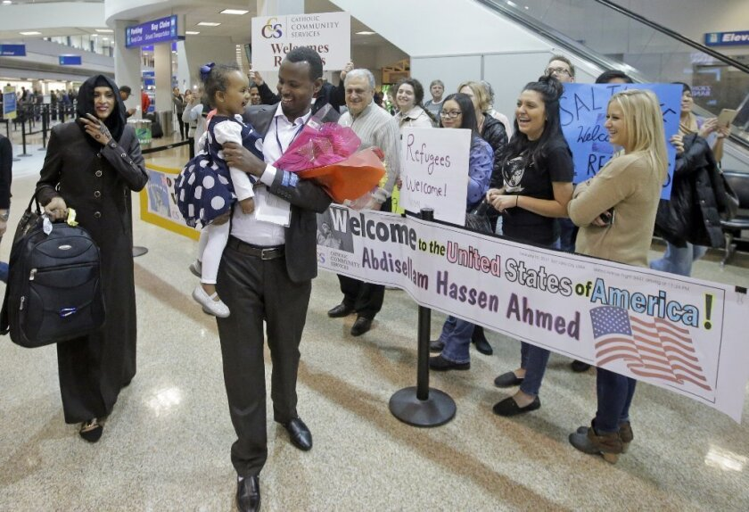 A Somali refugee family who had been stuck in limbo after President Donald Trump temporarily banned refugee entries gets a warm welcome at the Salt Lake City airport on Friday.