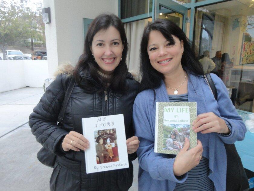 Students Yolanda Panniagua and Roxanna Zaibert show off their books containing their life stories.