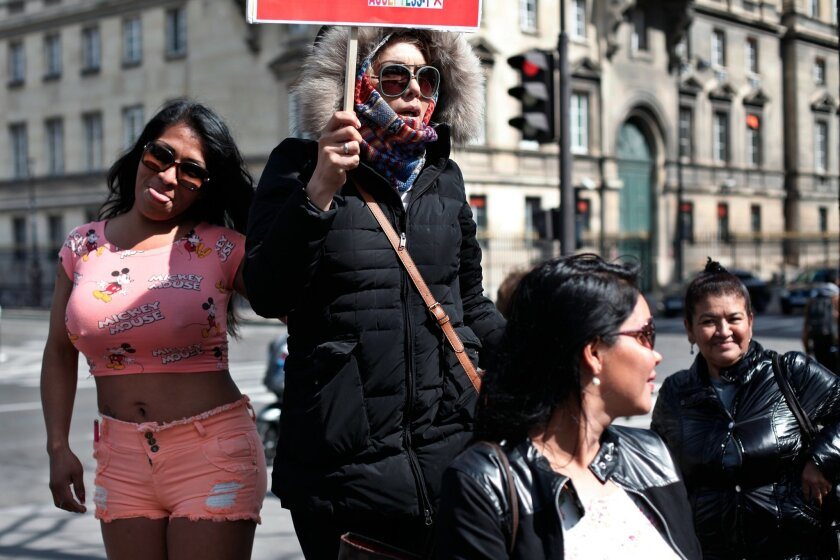 Sex workers hold signs during a protest against new bill against prostitution and sex trafficking, in Paris, Wednesday, April 6, 2016. (AP Photo/Thibault Camus)