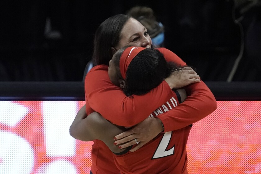 Arizona head coach Adia Barnes gets a hug from guard Aari McDonald (2) at the end of a women's Final Four NCAA college basketball tournament semifinal game against Connecticut Friday, April 2, 2021, at the Alamodome in San Antonio. Arizona won 69-59. (AP Photo/Morry Gash)