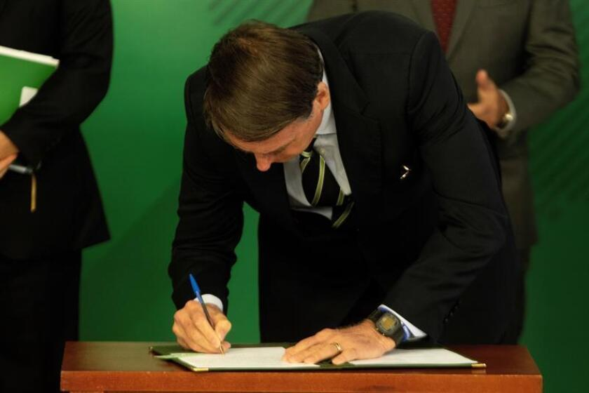 Ultra-rightist President Jair Bolsonaro on Jan. 15, 2019, signs a decree facilitating gun ownership in Brasilia, Brazil, thus fulfilling one of his main campaign promises. EFE-EPA/Joedson Alves