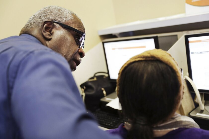 In this Thursday, March 3, 2016, photo, Georgia Department of Labor services specialist Louis Holliday, left, helps a woman with a job search at an unemployment office in Atlanta. On Thursday, March 31, 2016, the Labor Department reports on the number of people who applied for unemployment benefits a week earlier. (AP Photo/David Goldman)