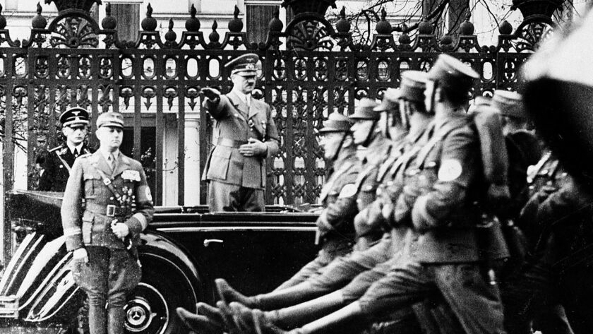 Nazi party leader Adolf Hitler is standing in an open cabriolet as he acknowledges a SA parade in ho