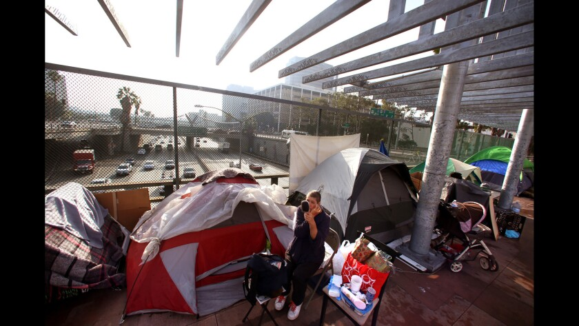 A woman holds a mirror as she sits in a folding chair near her tent in a homeless camp on a freeway overpass.