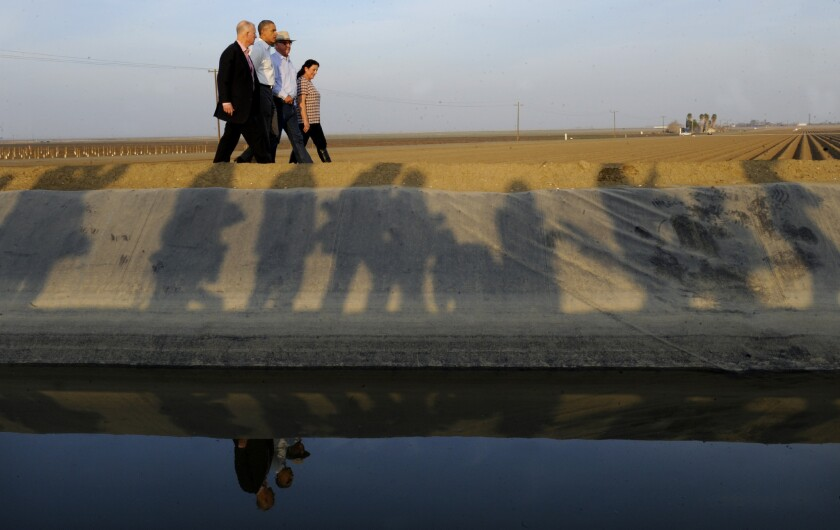 President Obama walks with California Gov. Jerry Brown, left, and a farm couple while discussing effects of the state drought during a visit to Los Banos, Calif.