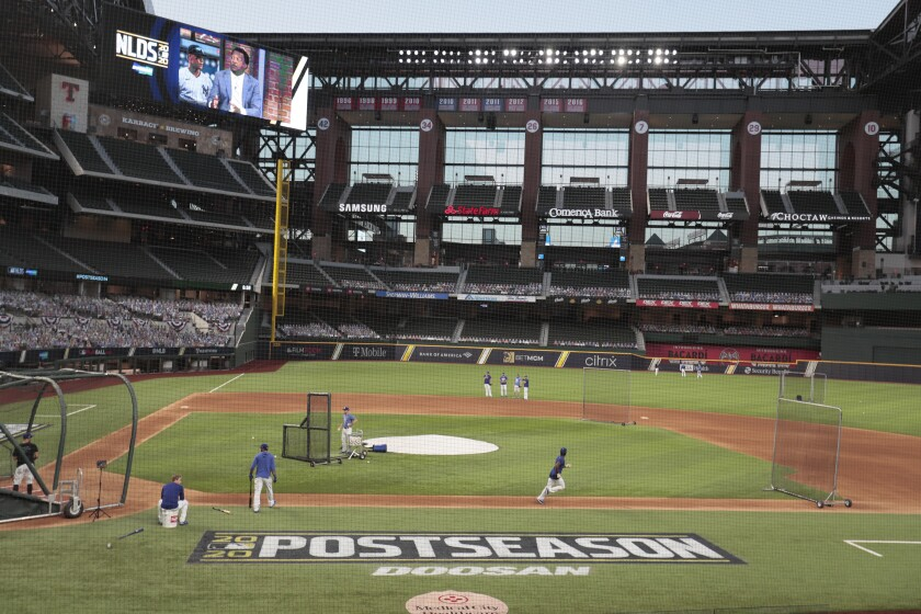 View from behind the first base-side dugout of Dodgers practicing at Globe Life Field in Arlington, Texas, on Monday.