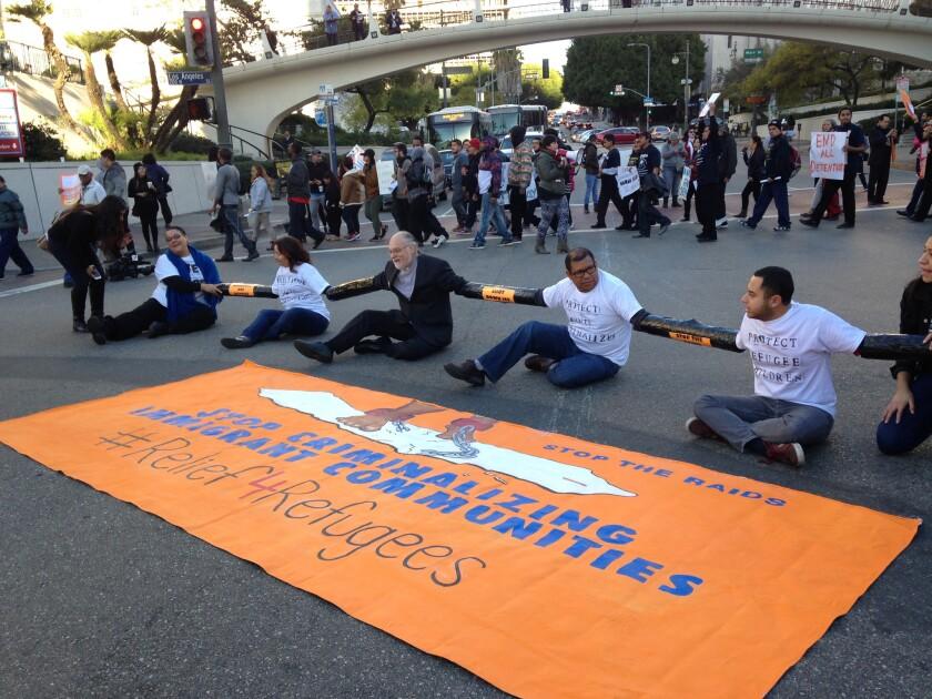 Immigrantes activistas unen sus manos en una manifestación contra las redadas y deportaciones en el centro de Los Angeles, EEEUU.Se manifestaron mientras decenas de simpatizantes marcharon en círculo gritando consignas en contra las deportaciones y una banda de trabajadores tocó temas relacionados a inmigrantes. (AP Photo/Edwin Tamara)
