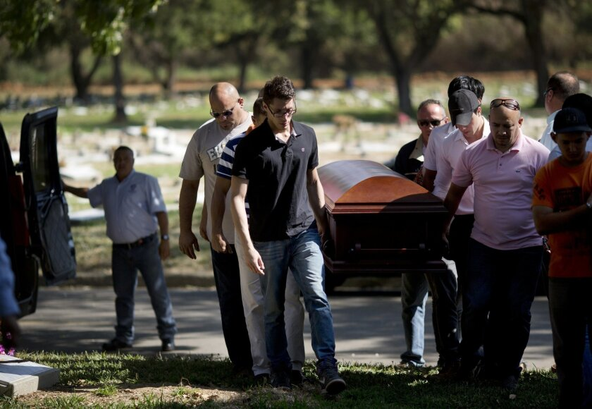 Relatives and friends carry the coffin of Genesis Carmona, in Valencia, Venezuela, Friday, Feb. 21, 2014. The university student and beauty queen was buried Friday in Valencia where she was slain during a political protest, a victim of what government opponents say is the kind of indiscriminate vio