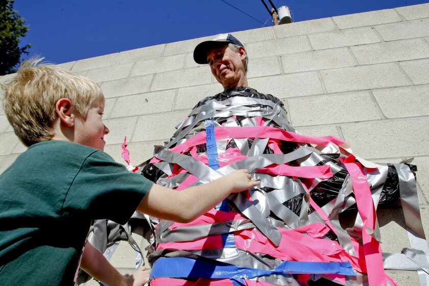 Eight-year-old Kevin Anderson places his piece of duct tape second grade teacher Tom Peterse, who was duct taped to a wall by students at the Light and Life Christian School in Escondido in 2013. Petersen did the stunt in an effort to raise money to buy students e-reader tablets.