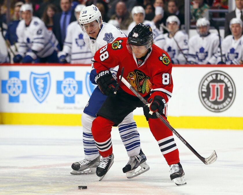 Chicago Blackhawks right wing Patrick Kane (88) battles Toronto Maple Leafs left wing Colin Greening (38) during the first period of an NHL hockey game on Monday, Feb. 15, 2016, in Chicago. (AP Photo/Jeff Haynes)