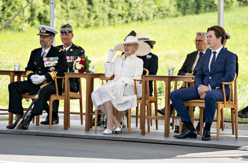 Denmark's Queen Margrethe, centre, Crown Prince Frederik and Prince Christian sit, during celebrations marking the 100th anniversary of the Reunification of Denmark and Southern Jutland, in Frederikshoej, Denmark, Sunday, June 13, 2021, during celebrations marking the 100th anniversary of the Reunification of Denmark and Southern Jutland. The Danish queen, German president and dignitaries from both the Scandinavian country and Germany marked Sunday the centennial of the 1920 reunification of Denmark in a celebration that was delayed by almost one year due to COVID-19.The reunification day of Denmark refers to June 15, 1920 when Danish King Christian X ratified a law that reunited the South Jutland region into Denmark after the area had been under German rule for 56 years. (Henning Bagger/Ritzau Scanpix via AP)