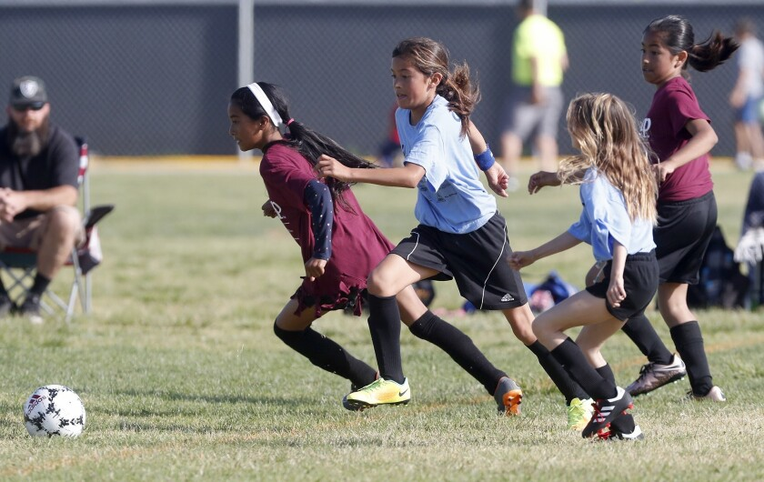 Costa Mesa California Elementary's Sophia Zarate, center, chases down a loose ball against Costa Mes