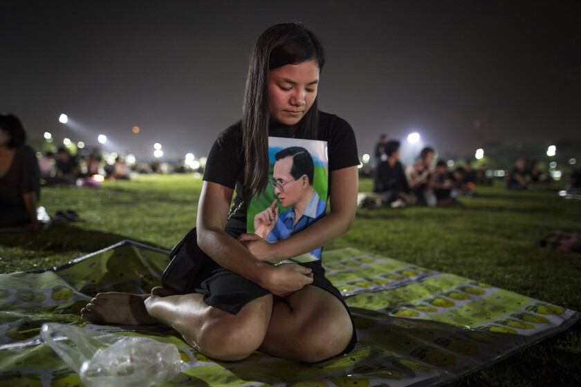 Thais pray and light candles Sunday in memory of their late king outside the Grand Palace in Bangkok, Thailand.