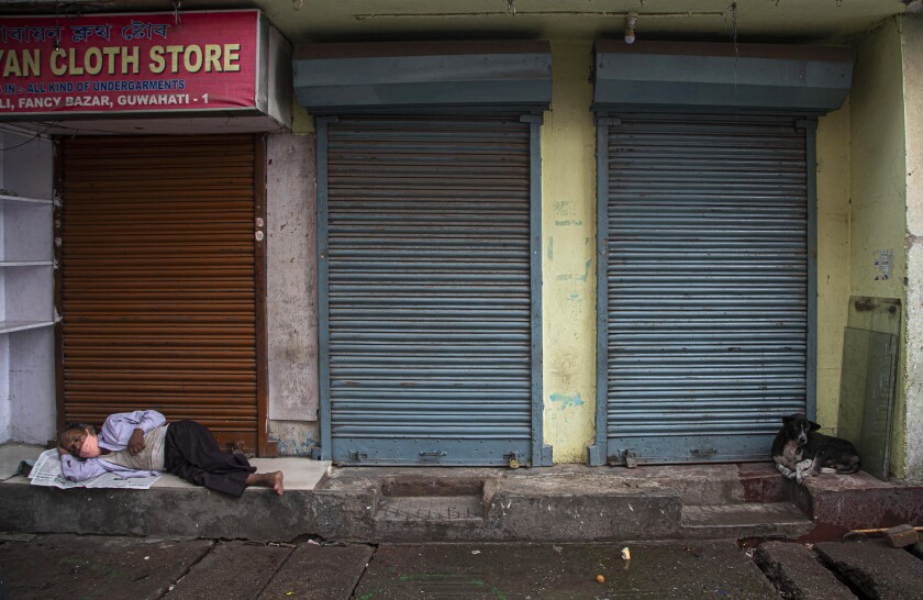 An Indian man wearing a face mask as a precaution against the coronavirus sleeps outside closed shops during the reimposed lockdown in Gauhati, India, Monday, June 29, 2020. India has reported a new daily record of nearly 20,000 new infections as several Indian states reimpose partial or full lockdowns to stem the spread of the coronavirus. (AP Photo/Anupam Nath)