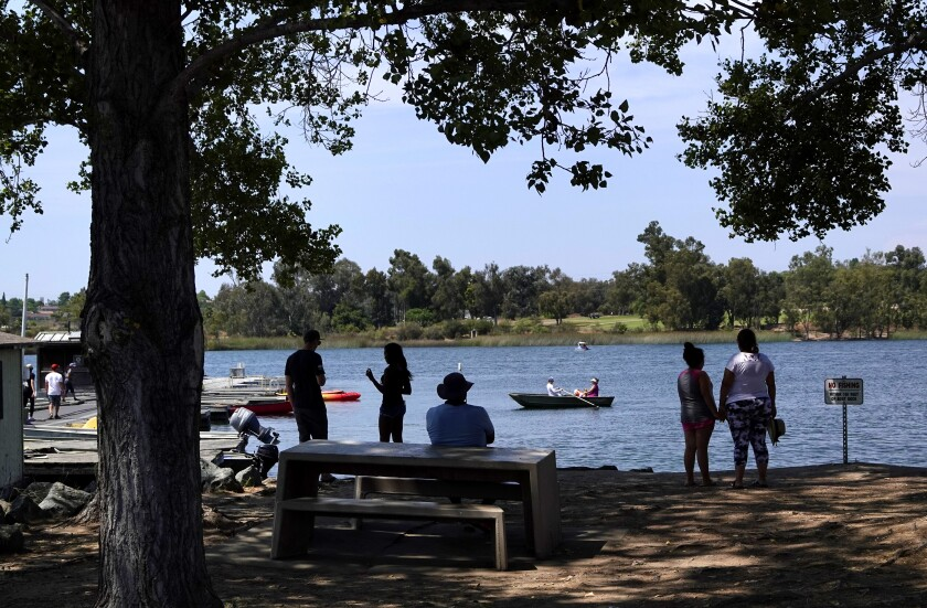 People stay in the shade as others row in a boat on Lake Murray.