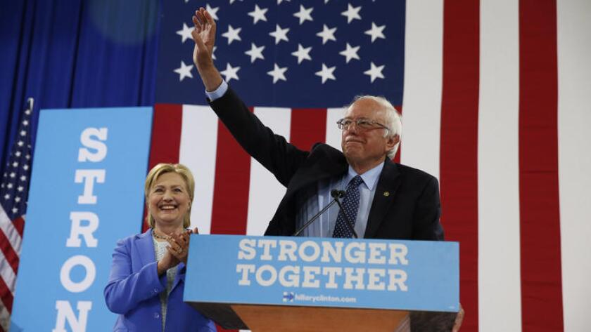 Sen. Bernie Sanders waves as he and Hillary Clinton arrive for a rally July 12 in Portsmouth, N.H.