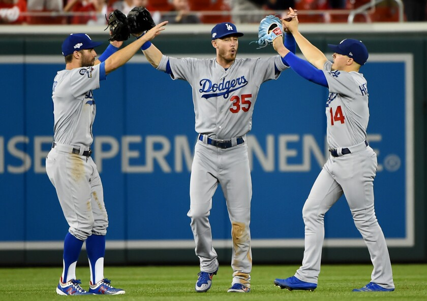 Dodgers outfielders Chris Taylor (3), Cody Bellinger (35) and Enrique Hernandez (14) celebrate after the final out of Game 3 of the NLDS to defeat the Washington Nationals 10-4 at Nationals Park on Oct. 06 in Washington, DC.