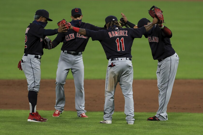 Cleveland Indians' Francisco Lindor, left, Cesar Hernandez, middle left, Carlos Santana, right, and Jose Ramirez, middle right, celebrate after a baseball game against the Cincinnati Reds in Cincinnati, Tuesday, Aug. 4, 2020. The Indians won 4-2. (AP Photo/Aaron Doster)