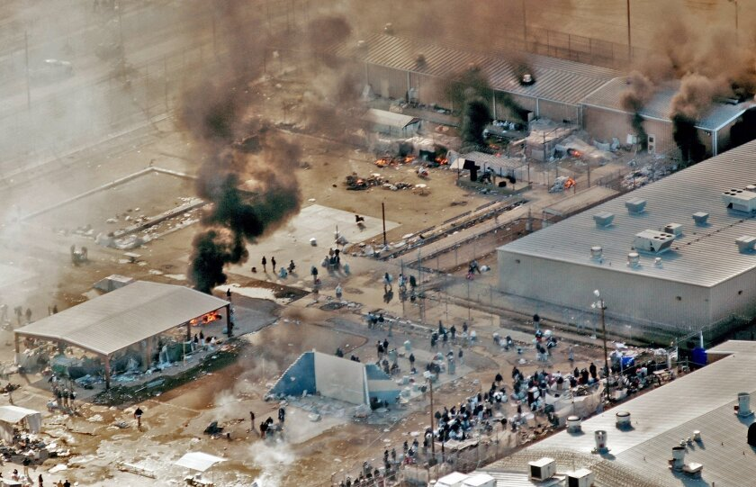"""FILE - In this Thursday, Feb. 5, 2009 file photo, plumes of smoke rise from the yard and recreation building of Reeves County Detention Center 1 unit in Pecos, Texas. The fires came five days after inmates set fires to other parts of the RCDC I and II units during a riot blamed on complaints about inadequate health care and food. A Justice Department Inspector General report released Thursday, April 23, 2015, was critical of the operation at the the 2,400-bed facility that primarily houses """"low-level"""" immigrants in the country illegally. (AP Photo/Pecos Enterprise, Smokey Briggs, file)"""
