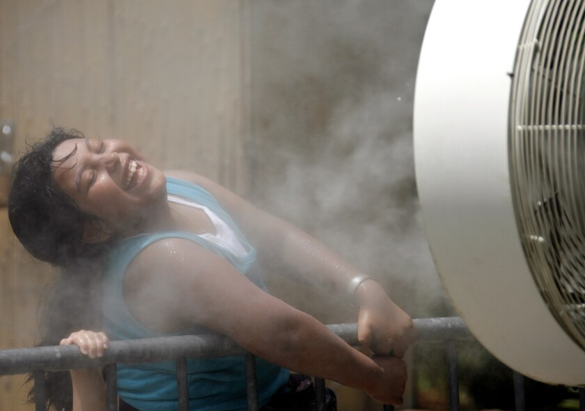 Cynthia Henriquez, 8, cools off from the heat in the mist of a fan set up for visitors at the Los Angeles Zoo on Wednesday, July 26, 2006. Starting Thursday, warmer weather will plague California.