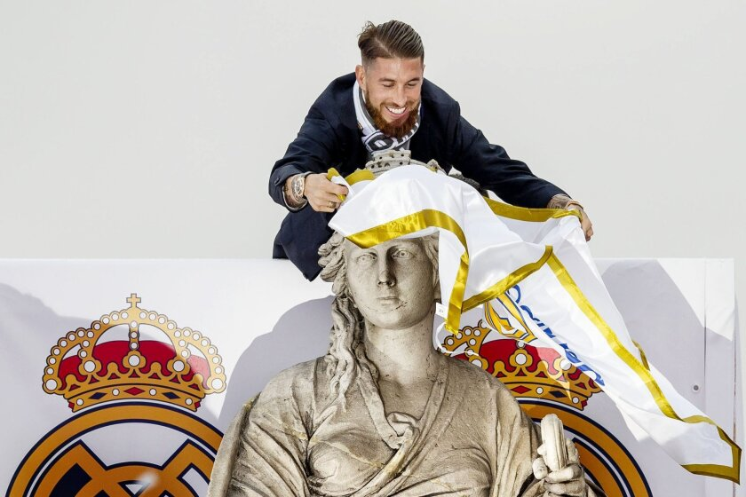 Real Madrid player Sergio Ramos ties a Real Madrid flag around the neck of goddess Cibeles monument as the team arrives at Cibeles square after winning the Champions League final soccer match between Real Madrid and Atletico Madrid, during a celebration parade in Madrid, Sunday, May 29, 2016. Real