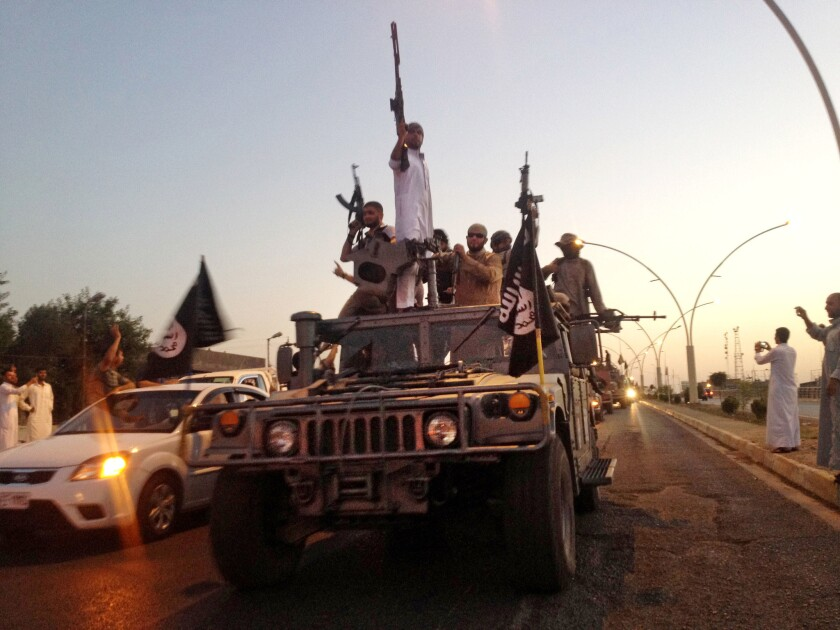 Fighters from Islamic State parade through Mosul in 2014 after taking the city.