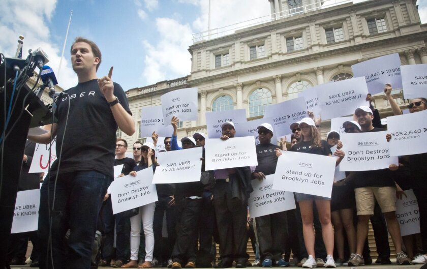FILE - In this June 30, 2015 file photo, Josh Mohrer, far left, New York's general manager for Uber, speaks during a news conference and rally outside New York's City Hall, while inside lawmakers were holding a hearing on the growth of the For-Hire-Vehicle (FHV) industry in the city, with a focus on Uber. A deal has been struck between New York City and Uber on the eve of a highly watched City Council vote that could have placed a cap on the number of the ride-hailing company's cars on the streets of the nation's largest city. (AP Photo/Bebeto Matthews, File)