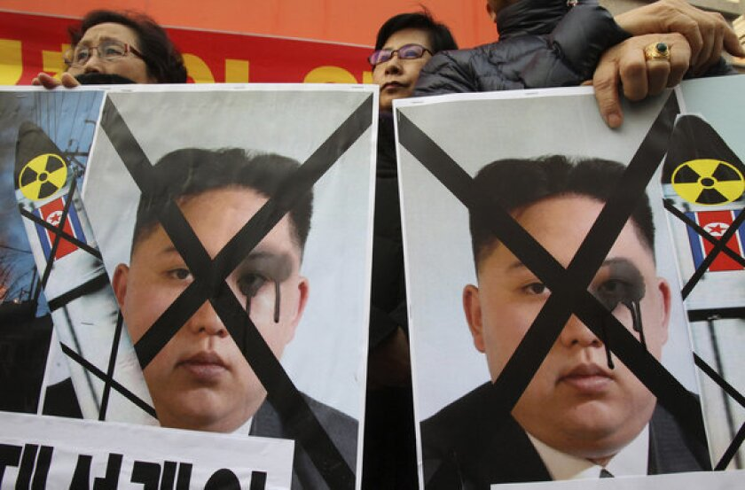 South Korean protesters hold defaced portraits of North Korean leader Kim Jong Un during a rally in Seoul against the north.