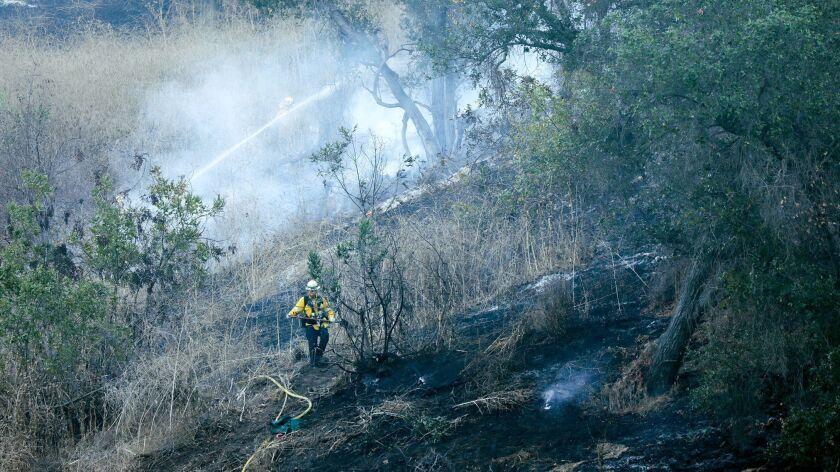 Firefighters mop up hot spots while battling two brush fires in the hills next to the 57 Freeway in Diamond Bar on Wednesday morning.