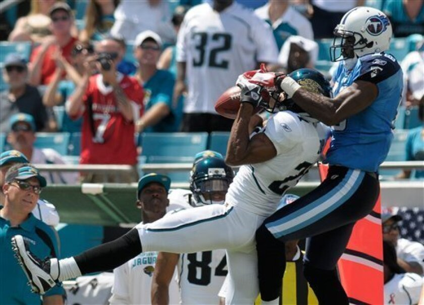 Jacksonville Jaguars defensive back Derek Cox (21), left, catches a pass in front of Tennessee Titans wide receiver Kenny Britt, right, but was ruled out of bounds during the first half of an NFL football game in Jacksonville, Fla., Sunday, Sept. 11, 2011. (AP Photo/Phelan Ebenhack)