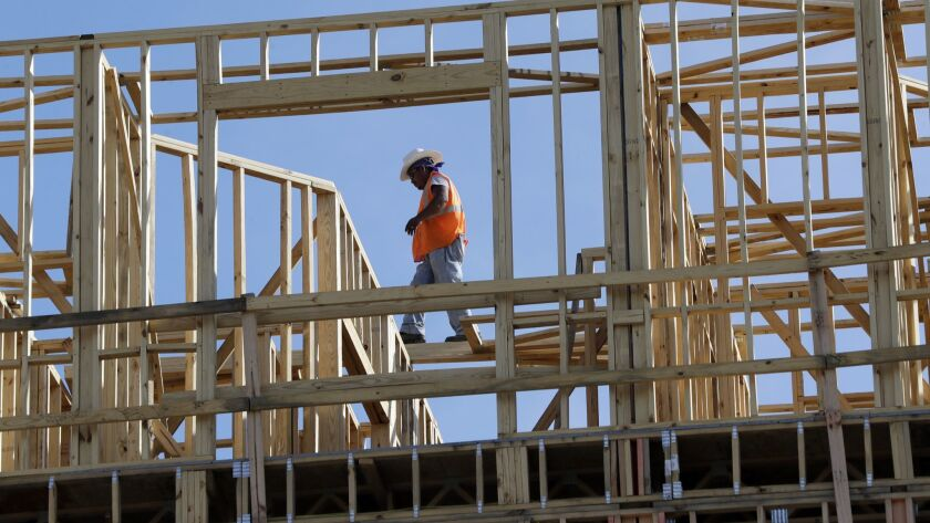 FILE - In this Oct. 6, 2017, file photo, workers build an apartment and retail complex in Nashville,