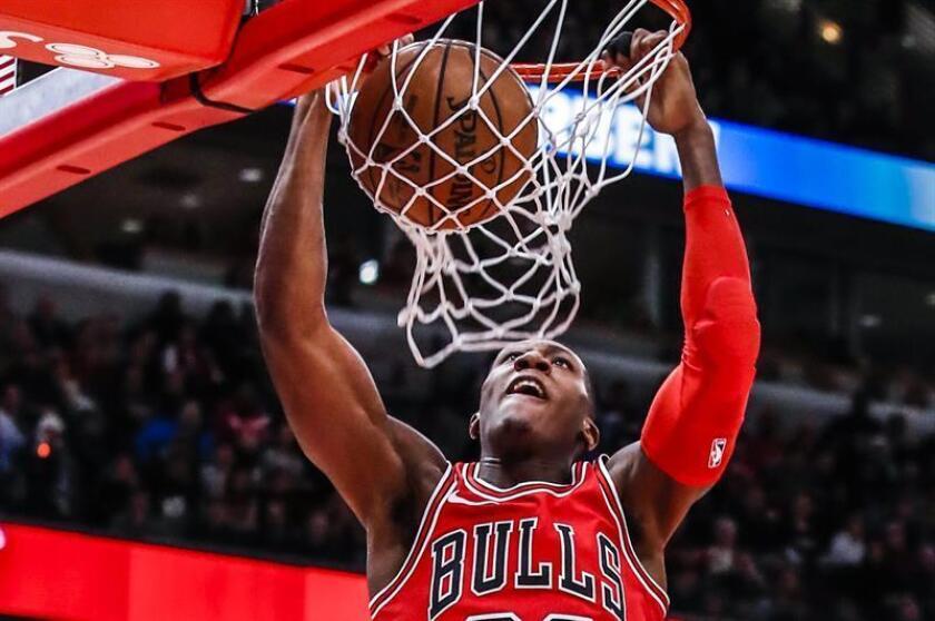 Kris Dunn, base de los Bulls de Chicago, fue registrado este miércoles al volcar un balón en el aro que defendían los Knicks de Nueva York, durante un partido de la NBA, en el United Center de Chicago (Illinois, EE.UU.). EFE