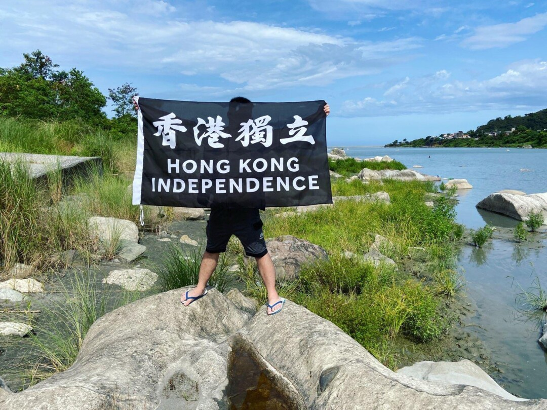 """A young man standing on rocks near water holds a sign reading, """"Hong Kong independence"""""""