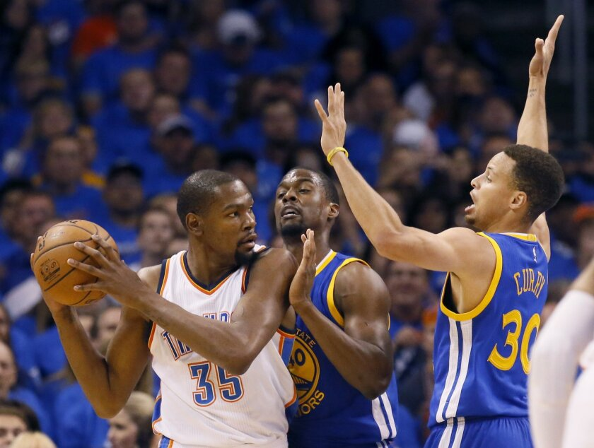 Oklahoma City Thunder forward Kevin Durant (35) is guarded by Golden State Warriors forward Harrison Barnes (40) and guard Stephen Curry (30) during the first quarter in Game 3 of the NBA basketball Western Conference finals  in Oklahoma City, Sunday, May 22, 2016. (AP Photo/Sue Ogrocki)